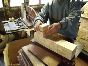 Uniformly cut hinoki pieces are neatly piled on each other to prepare them for the joint cutting